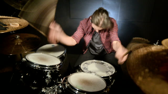 vidéos et rushes de les batteurs aux cheveux longs jouent le kit de batterie dans une pièce foncée sur un fond noir. musicien de rock. - instrument à percussion