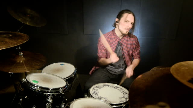 vídeos de stock e filmes b-roll de long-haired drummers play drum kit in a dark room on a black background. - baterista