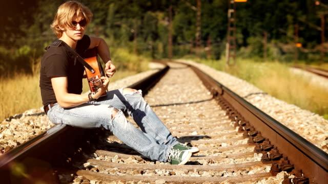 långhårig gitarrist sitter på järnvägen spelar bär grön duk skor - akustisk gitarr bildbanksvideor och videomaterial från bakom kulisserna