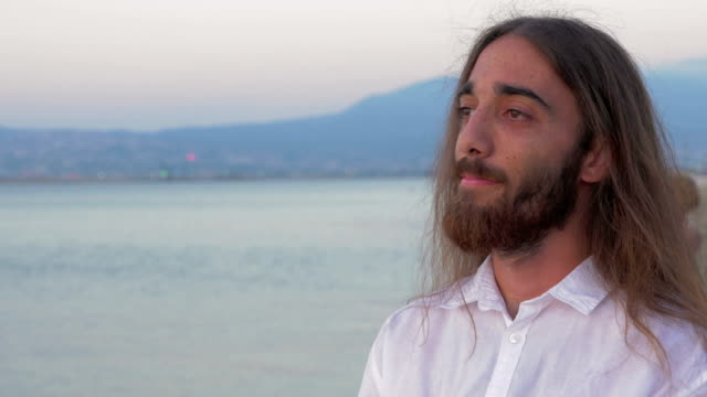 długo haired człowiek z brodą na plaży - długie włosy filmów i materiałów b-roll