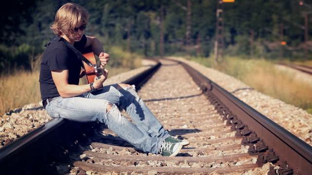 Long-haired teenage guitarist sitting on railway tracks strumming strings on acoustic guitar