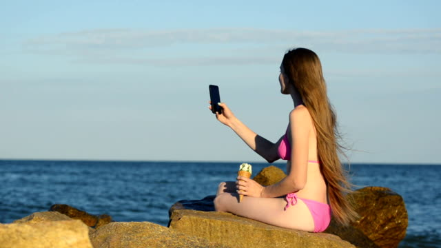Long-haired young woman sitting on the beach and take pictures on the phone