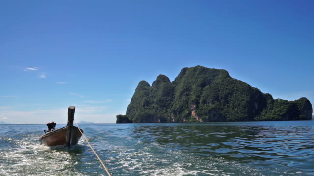 Longtail boat summer holiday excursion Thailand A boat journey across the Andaman sea, Krabi province, Thailand.  Takes us past Ko Talabeng islands.  These stunning limestone karst cliffs rise from the sea, leaving tourists in awe of their beauty.  Tracking shot from the back of a boat, towing a traditional Longtail boat. towing stock videos & royalty-free footage