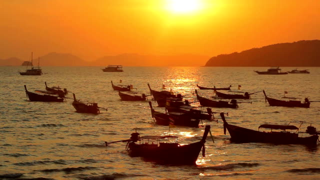 Longtail boats on seashore at sunset video