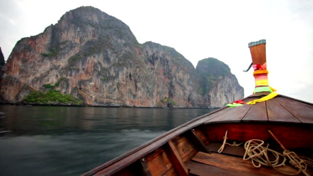 Longtail, the traditional Thai boat, floats by rocky islands video