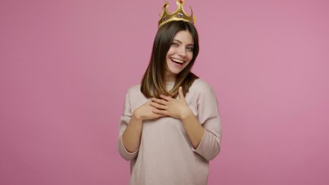 vidéos et rushes de regarde la reine ! femme brune égoïste attirante portant la couronne d'or, se sentant arrogante confiante, fière de sa beauté - couronne reine