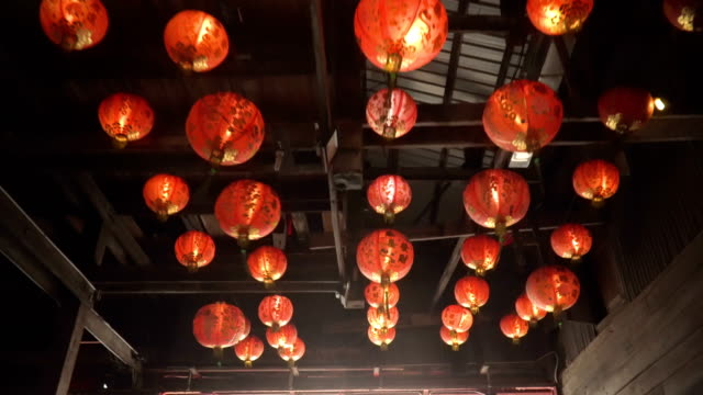 look at red asian lanterns under wooden buliding - lanterna attrezzatura per illuminazione video stock e b–roll