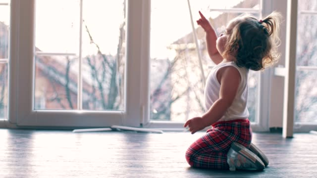 Look at that! Baby girl (14 months) kneeling by the window at home, looking up pointing at something with her finger, exploring the environment. pointing stock videos & royalty-free footage