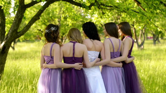 look from behind of emotional bride and bridesmaids that talking and smiling. caucasian girls in purple dresses posing outdoors. - wedding fashion stock videos and b-roll footage