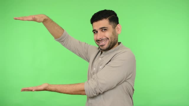Look here! Happy satisfied brunette man in shirt holding palm and pointing copy space. studio shot, green background, chroma key