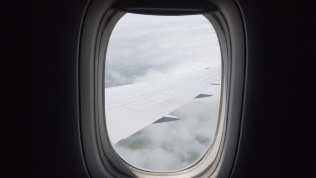 look outside of airplane window onto moving clouds with view on wing - skrzydło samolotu filmów i materiałów b-roll