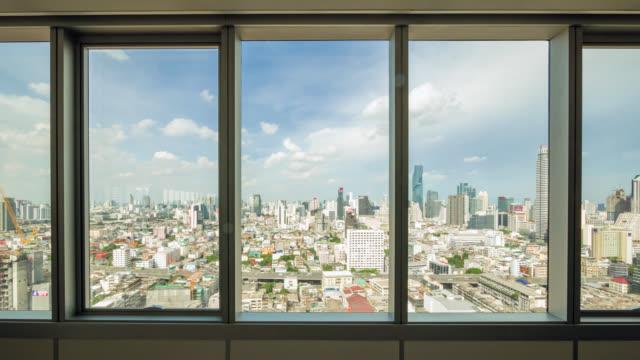vídeos de stock, filmes e b-roll de olhe através da exibição de cidade e o tráfego em bangkok da janela do escritório - janela