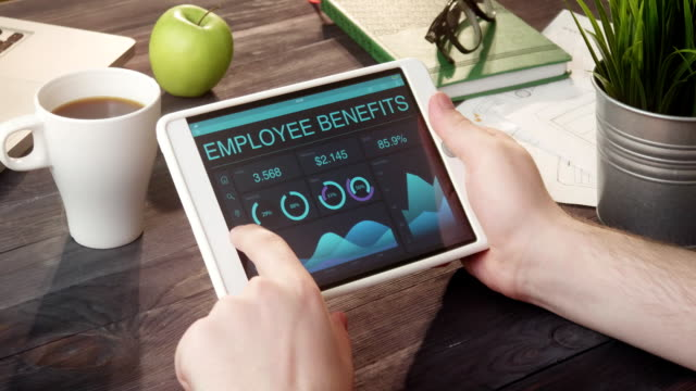 Looking at employee benefits records using digital tablet at desk video