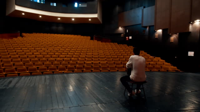 Looking at empty theater There is one young man, age 23. He is in theater and he have a rehearsal. He is an actor,he read and learn his text. performer stock videos & royalty-free footage