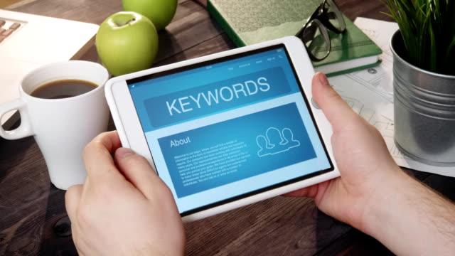 vídeos y material grabado en eventos de stock de mirando en la página de internet de palabras clave con tableta digital - seo