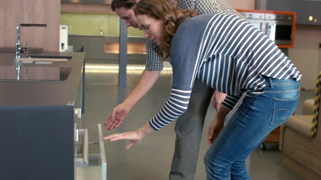 Looking at kitchen products in showroom Couple browsing sample kitchens in showroom, opening drawers to see finishes and test mechanisms furniture stock videos & royalty-free footage