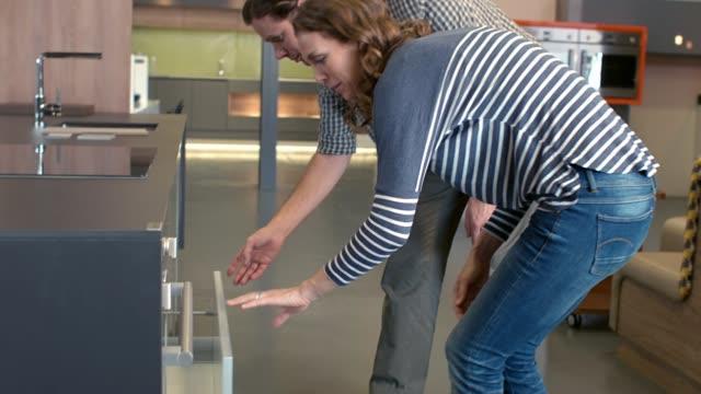vídeos de stock, filmes e b-roll de olhando para produtos de cozinha na sala de exposições - mobília