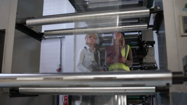 Looking at machinery Two female managers looking and reviewing machinery at their factory production line worker stock videos & royalty-free footage