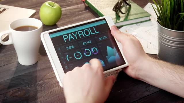 Looking at payroll records using digital tablet at desk