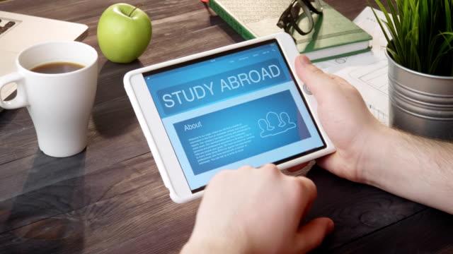 La recherche à l'étude à l'étranger web page à l'aide de tablette numérique au comptoir - Vidéo
