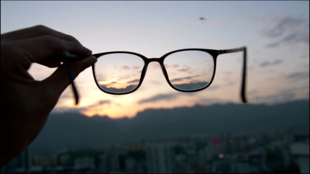 looking city sunset through eyeglass - trasparente video stock e b–roll