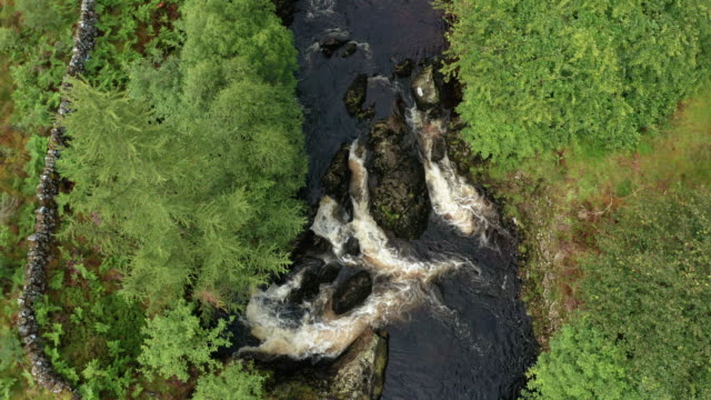 Looking down on a fast moving water in a small Scottish river in rural Dumfries and Galloway, south west Scotland video