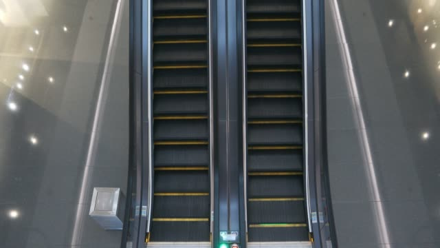 looking down on an empty escalator in a shopping mall - escalator video stock e b–roll