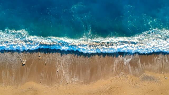 vídeos de stock e filmes b-roll de looking down onto waves on the beach - maré