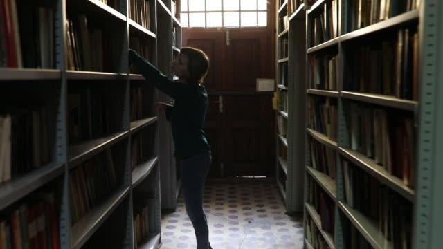 stockvideo's en b-roll-footage met op zoek naar de perfecte boek - boekenkast