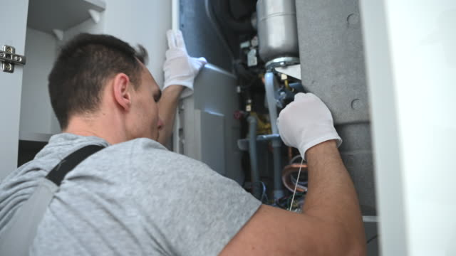 Looking Inside Central Gas Heater Trying to Fix the Problem Caucasian Worker Looking Inside Central Gas Heater Trying to Fix the Problem. furnace stock videos & royalty-free footage