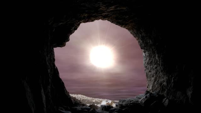 tittar ut en grotta entré som solen skiner in i graven mot en dramatisk lynnig himmel - ljus på grav bildbanksvideor och videomaterial från bakom kulisserna