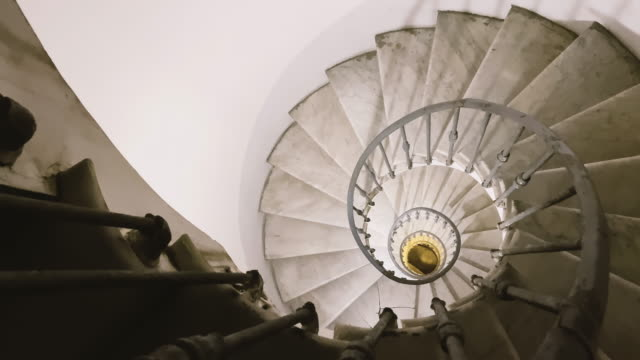 looking out from the top of an ancient spiral staircase with iron handrails and marble steps