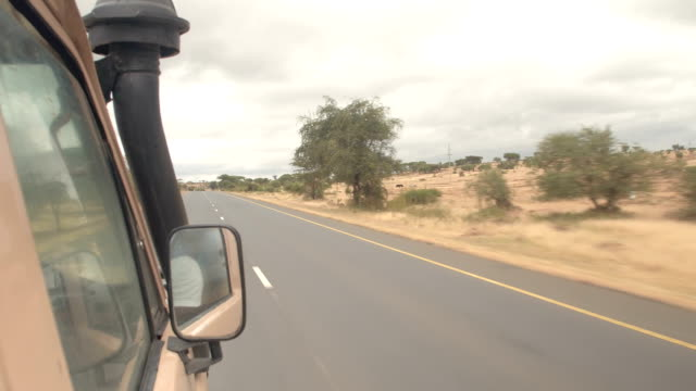 close up: looking out the window while safari jeep driving past massai people - mandriano video stock e b–roll