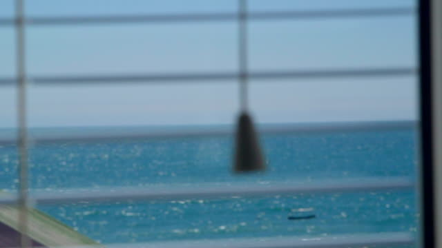 Looking out through the open window blinds at sea with floating boat video