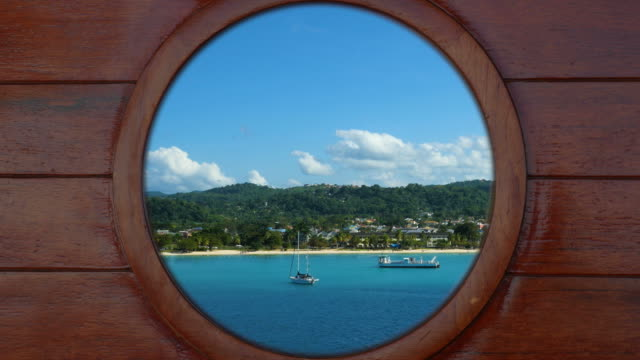 Looking outside through a porthole of a cruise ship to the beach