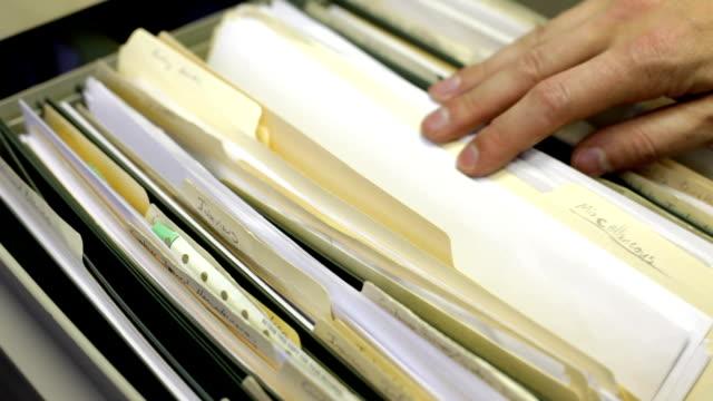 guardando attraverso i file nel cassetto della scrivania - schedario documento video stock e b–roll