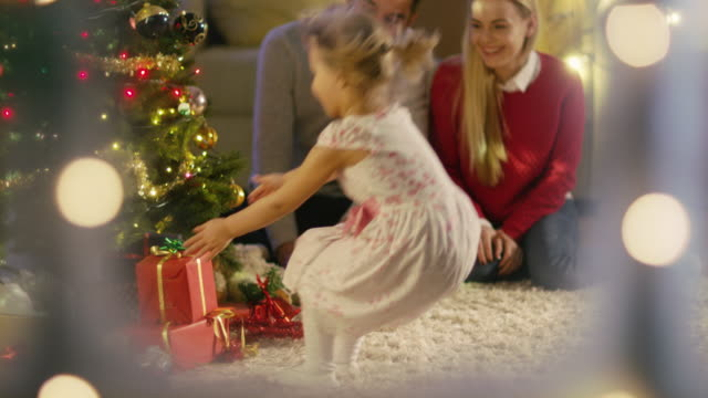 Looking Through Snowy Window. Happy Father, Mother and Daughter Sitting Under Christmas Tree. Daughter Gives a Gift to Her Mother. video