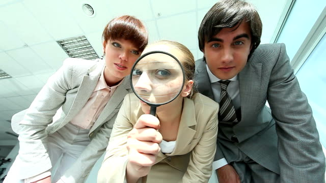 Looking through spy glass Group of business people looking through magnifying glass magnifying glass stock videos & royalty-free footage