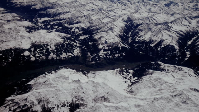 vídeos de stock e filmes b-roll de looking through the window aircraft during flight a snow covered italian and osterreich alps with blue sky without clouds. - montanha costeira