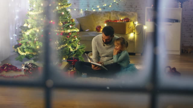 vídeos de stock e filmes b-roll de looking through the window. sitting under christmas three with gifts under it father reads book to his daughter. - pai solteiro