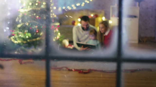 vídeos de stock e filmes b-roll de looking through the window. sitting under christmas three with gifts under it father and mother read a book to little daughter. - family christmas