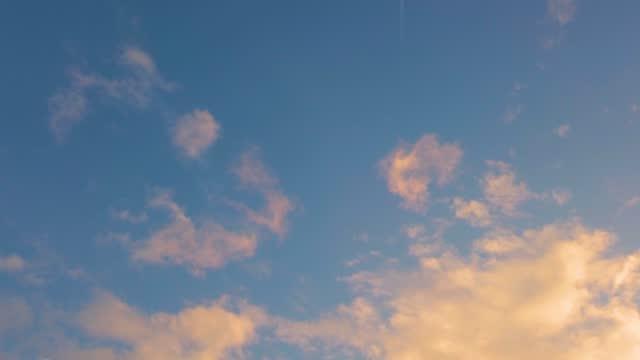 朝日光の中でリアルタイムで高速に動くカラフルな雲とジェット飛行機と青空を見上げる - ローアングル点の映像素材/bロール
