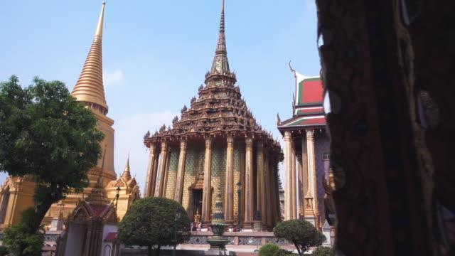 vídeos de stock, filmes e b-roll de olhando para a arquitetura do templo tailandês. wat phra kaew, templo do buda de esmeralda em banguecoque, tailândia. panorâmica tiro - característica arquitetônica