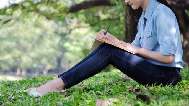stockvideo's en b-roll-footage met opzoeken voor inspiratie tijdens het wandelen buiten in de groene lente park tuin. close-up van jonge vrouw handen het neerschrijven van haar hoop en de dromen van toekomstige in haar dagboek, het maken van plannen. planner te doen - bord bericht