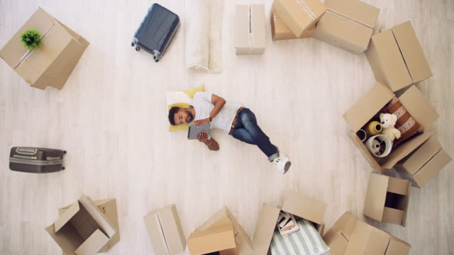 Looking up new ways to style up his new home 4k video footage of a handsome young man using a digital tablet while lying on the floor on moving day in his new home home ownership stock videos & royalty-free footage