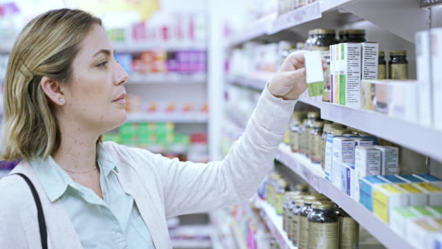 Looks good to me 4k video footage of a young woman browsing the shelves of a pharmacy pharmaceutical industry stock videos & royalty-free footage