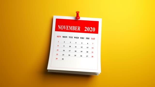 loop november month page of calendar 2020 year on yellow background - ноябрь стоковые видео и кадры b-roll