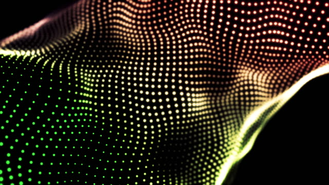 Loopable gradient waving dotted texture with shining blurred particles. Animation. Green, red, and yellow small circles flowing on black background, abstract fabric video