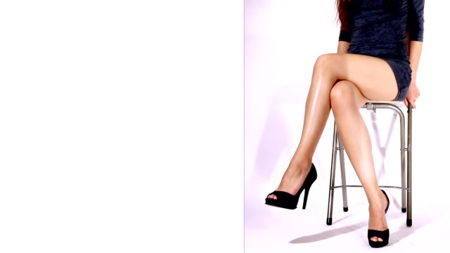 Loopable video of sexy legs of a young kittenish woman Young woman with sexy legs, shaking her legs in a kittenish style and getting attention. White part is for any kind of text, logo or message additions and commercial use. cross legged stock videos & royalty-free footage