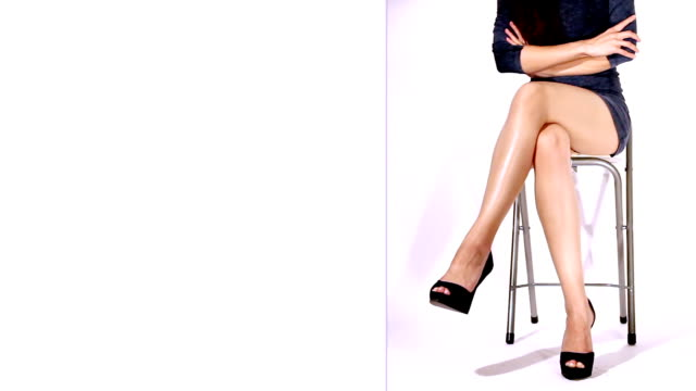 Loopable video of sexy legs of a young serious woman Young woman with sexy legs, shaking her legs in a serious style and getting attention. White part is for any kind of text, logo or message additions and commercial use. cross legged stock videos & royalty-free footage
